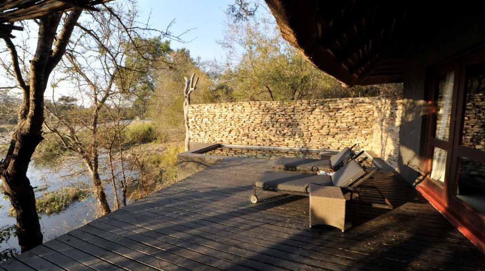 Une terrasse avec des chaises longues au Chitwa Chitwa