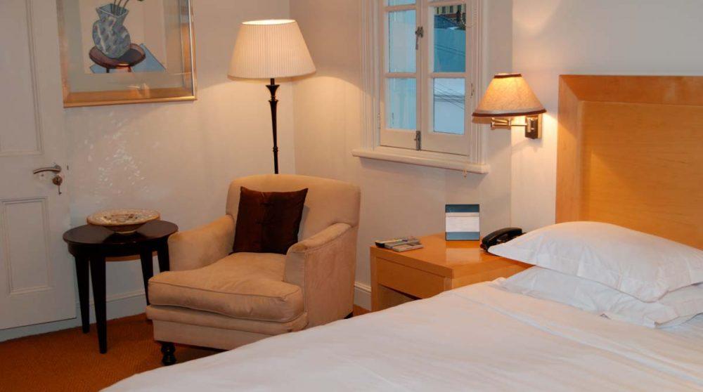 Fautueil et lit dans une chambre au Cap